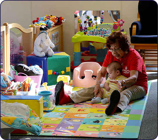 infant sitting with teacher