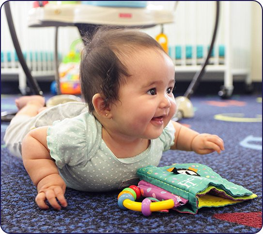 baby smiling while playing at infant daycare in Harrison