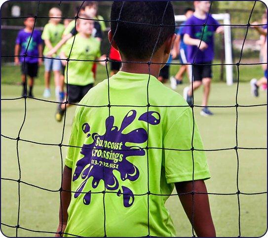 Boy playing soccer at summer camp