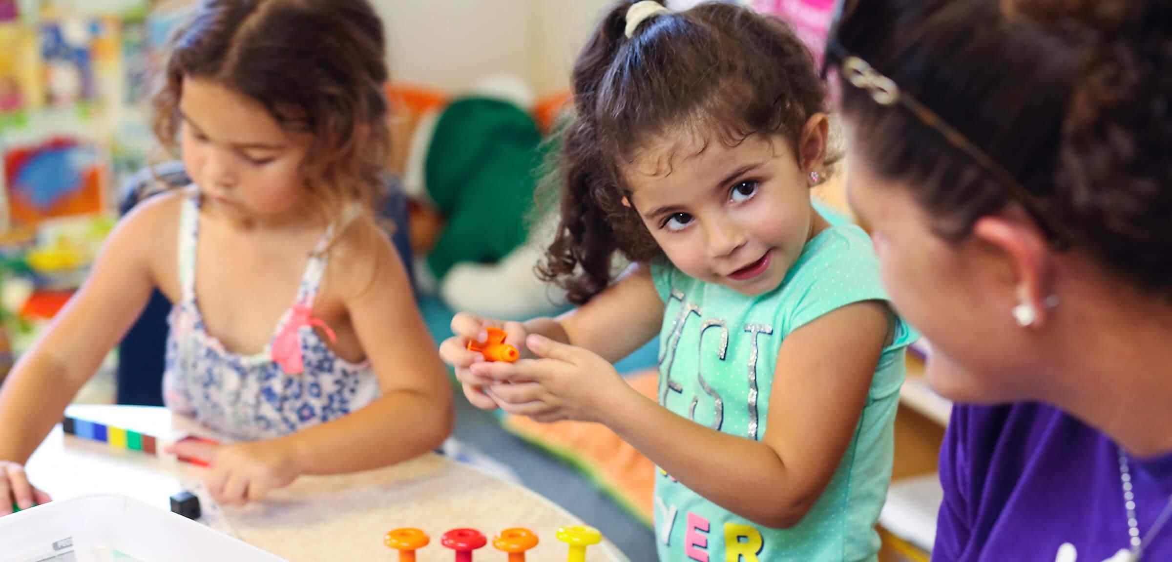 Two children and teacher at our preschool in Alpharetta