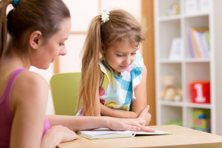 teacher helps student with homework at our after school programs in Canton GA