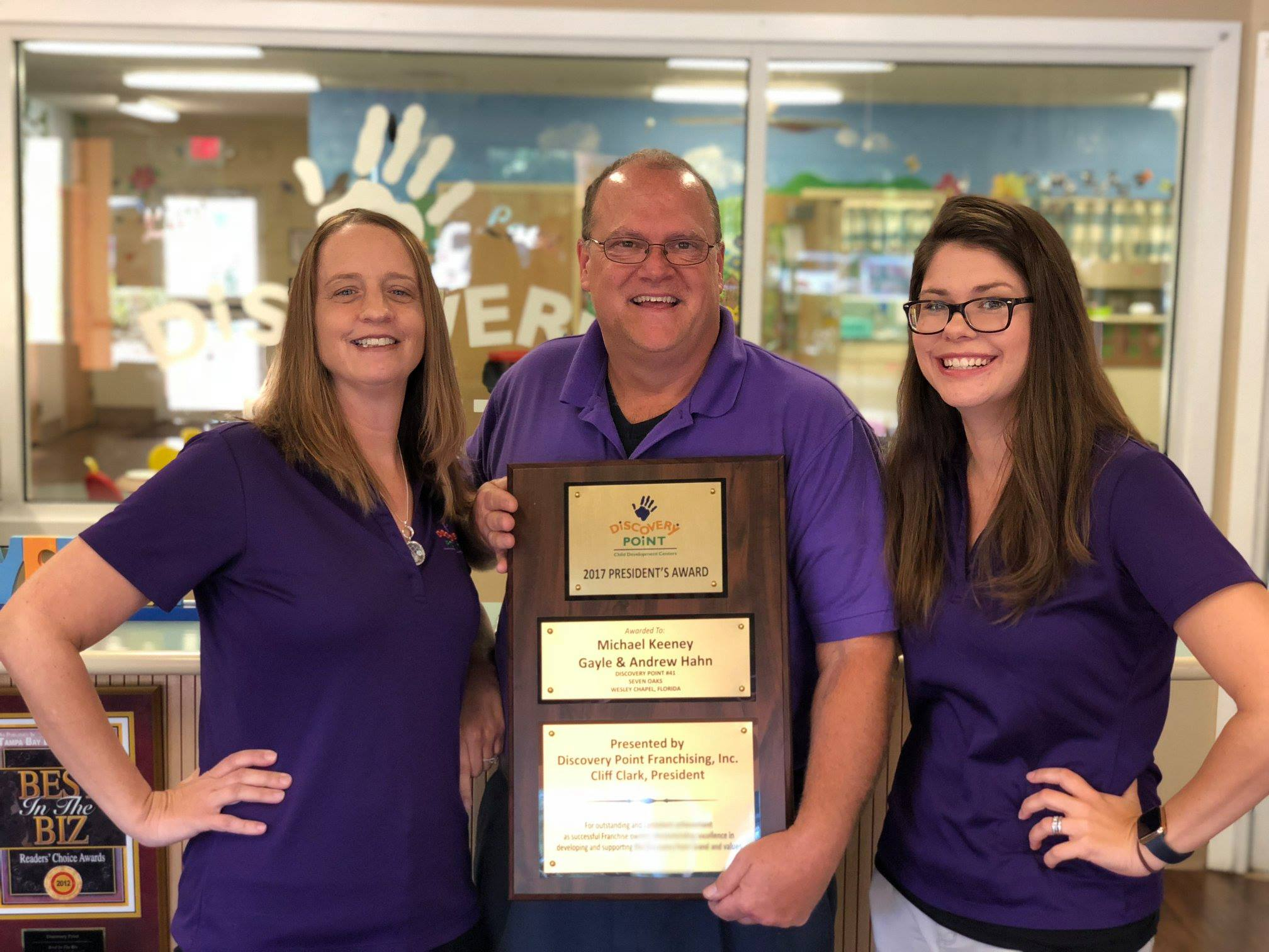 daycare franchise owner and staff with award