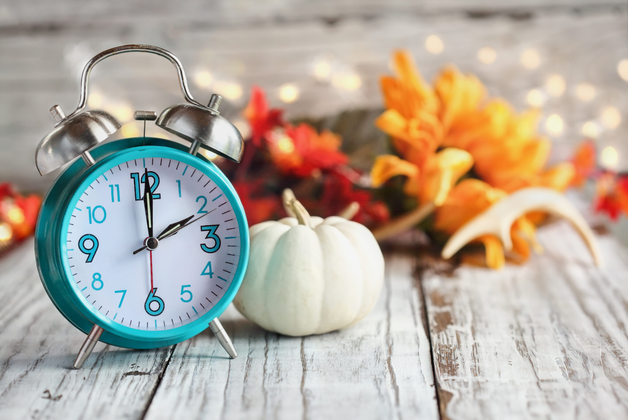 blue clock, white pumpkin, fall leaves, time change