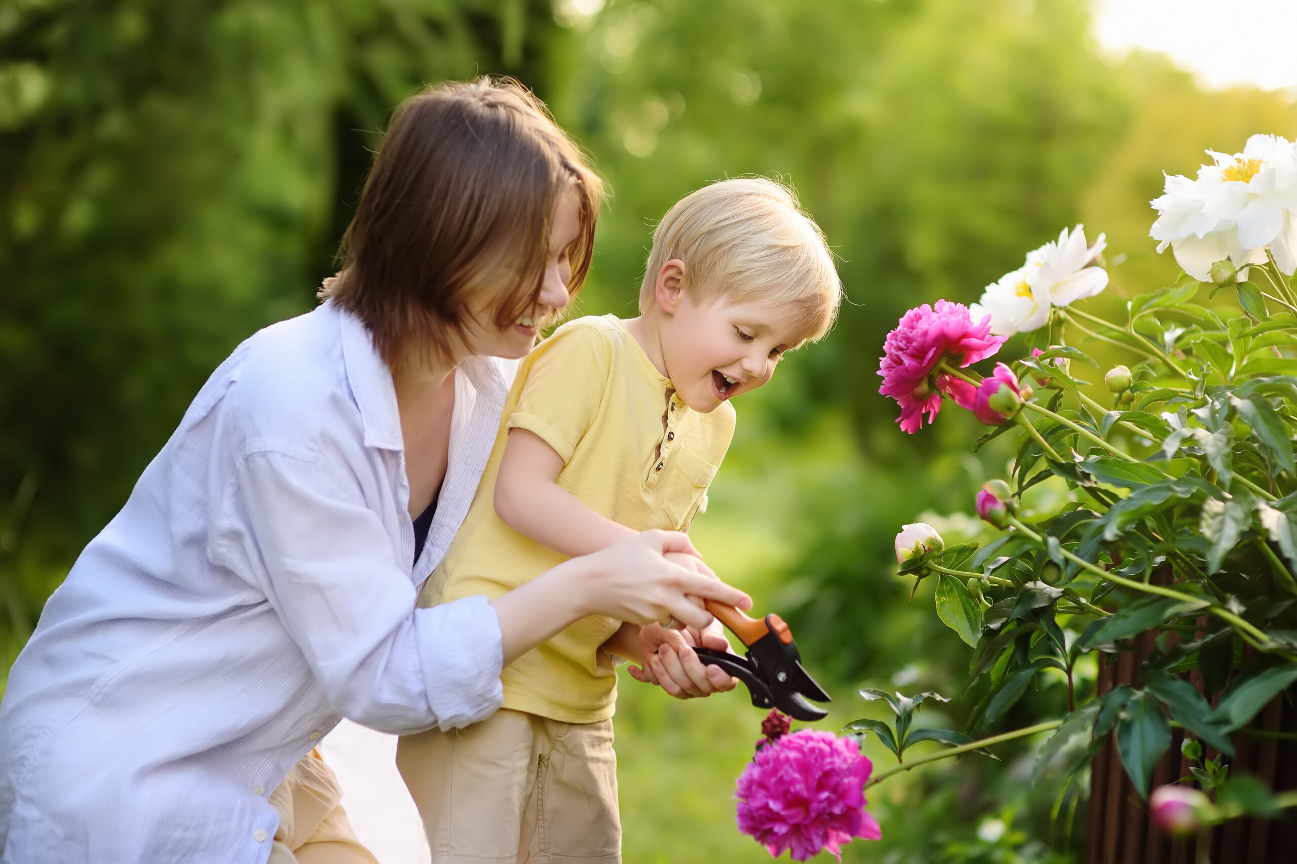mom and child cutting flowers in garden