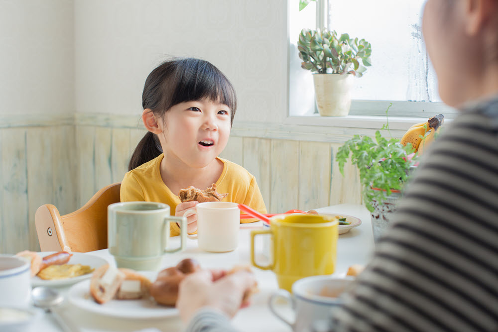 girl sits at table having conversation with dad